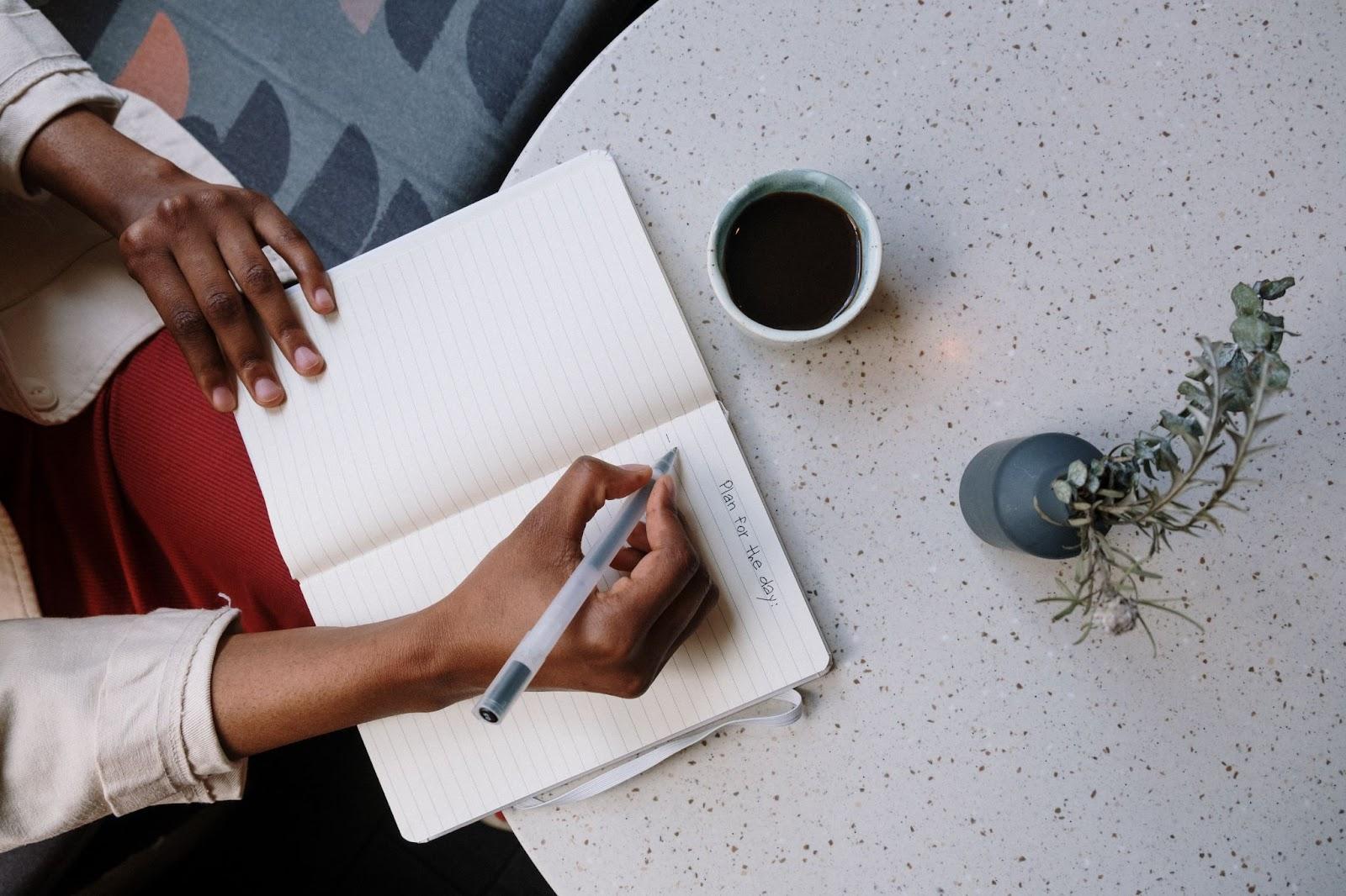 Woman journaling on a desk.