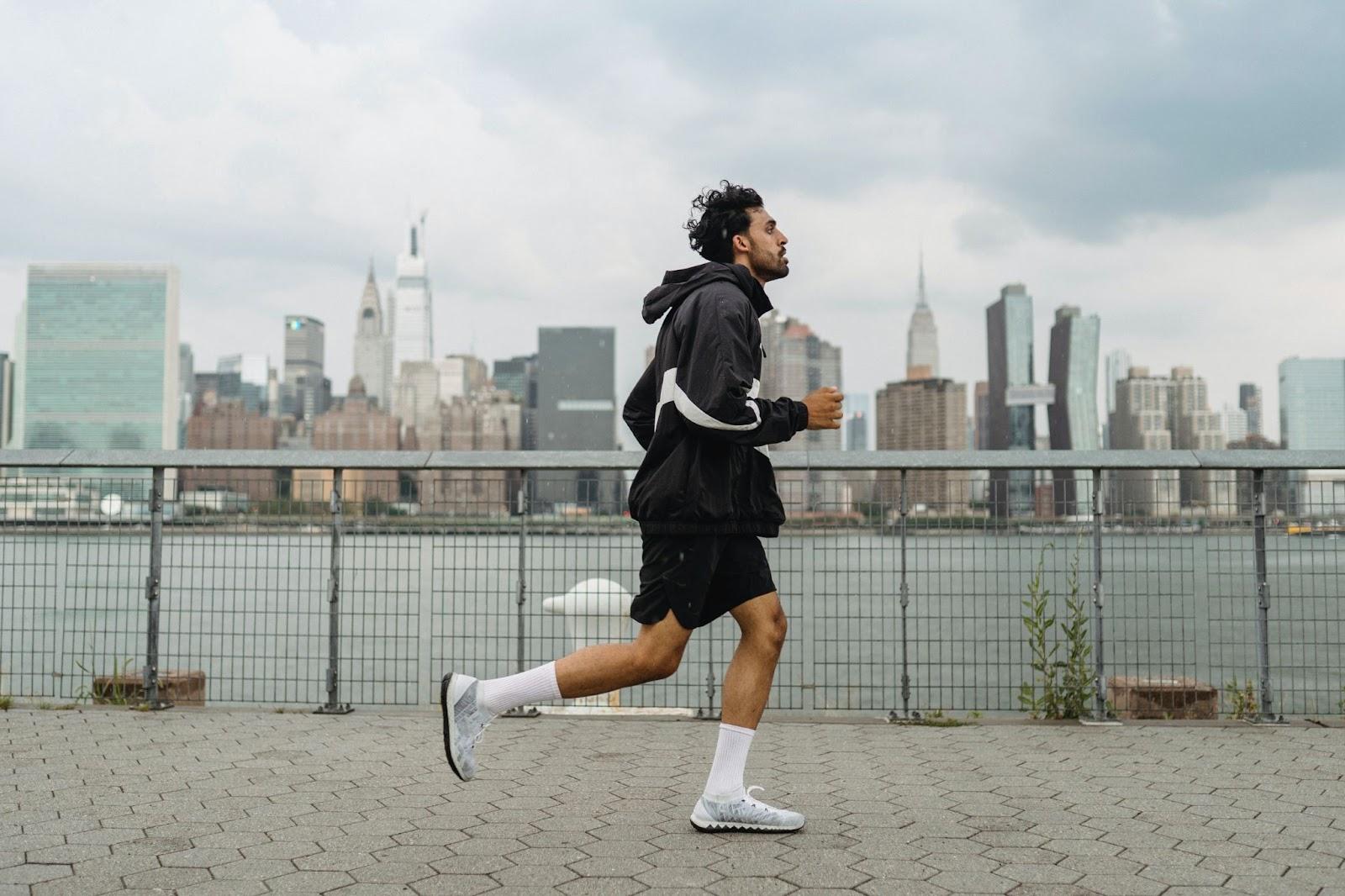 Man running on sidewalk nearby a cityscape.