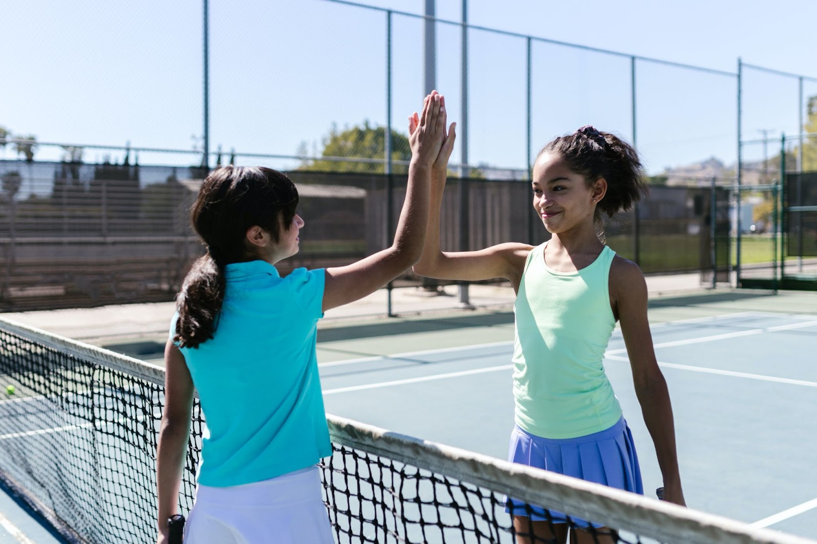 Two girls high-fiving each other after a tennis match.