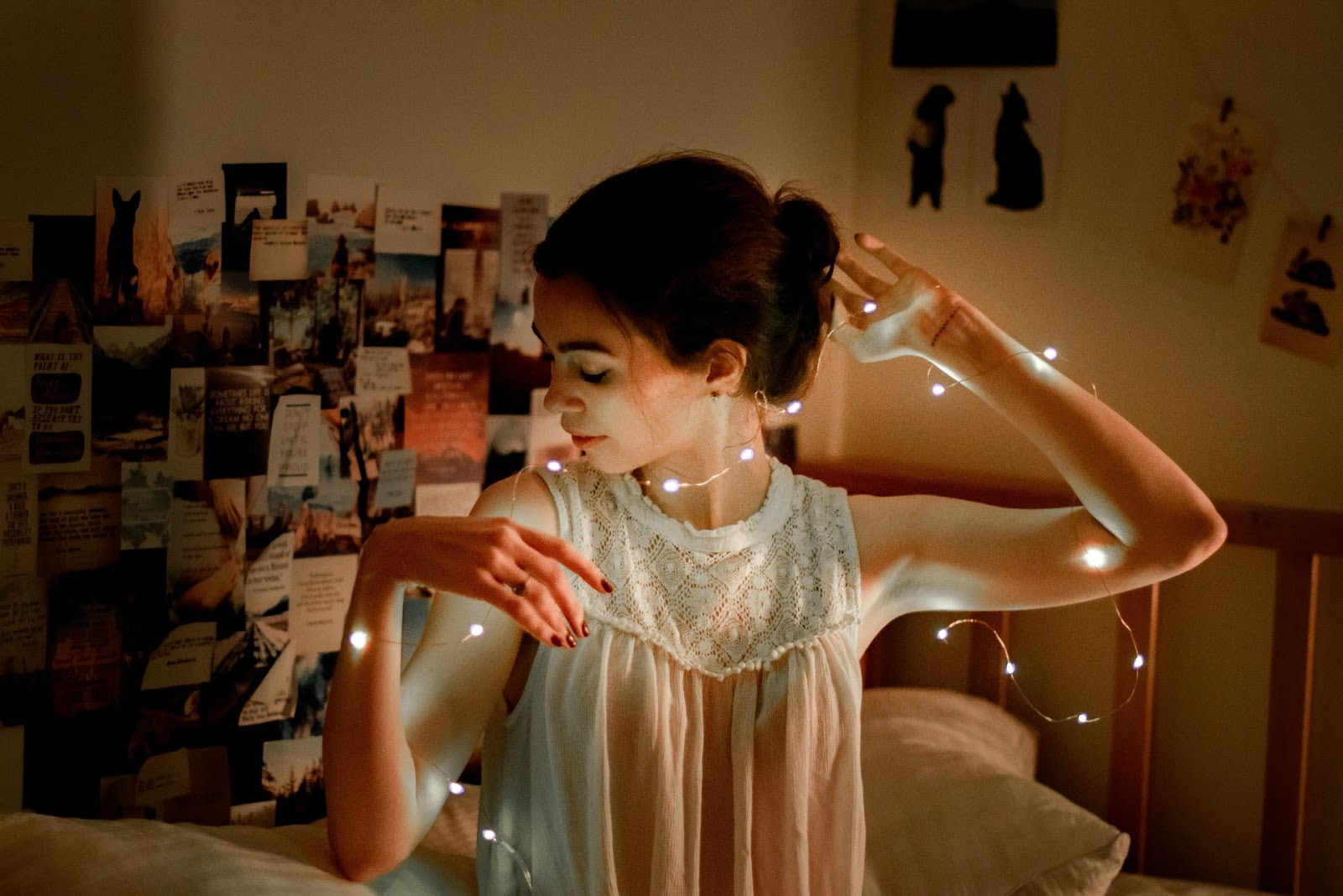 Girl draping string lights around herself.