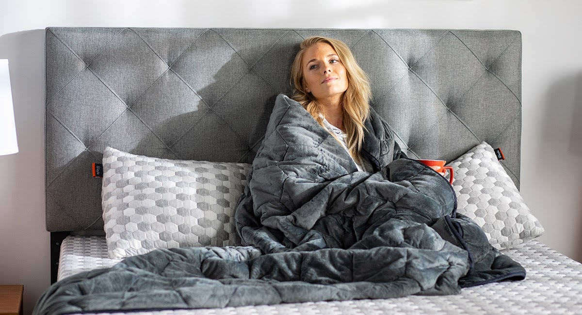 A picture of a woman snuggled up in a weighted blanket.
