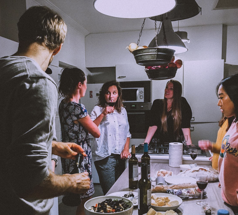 group of adult friends sipping wine around a counter in the kitchen