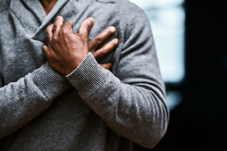 A man in a gray sweater grips his chest in pain.