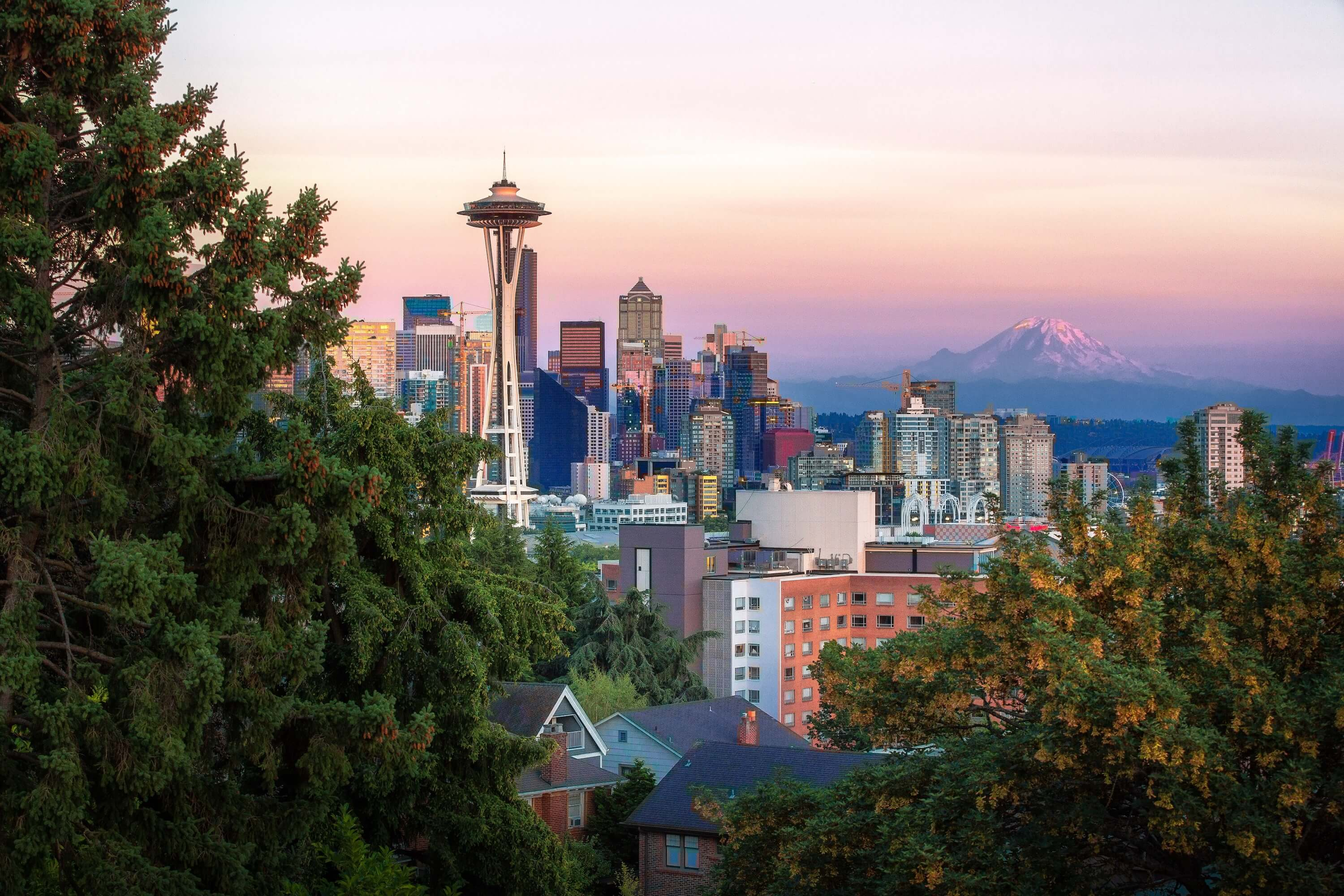 The Seattle skyline is seen at sunset with Mount Ranier in the background and lush greens in the foreground