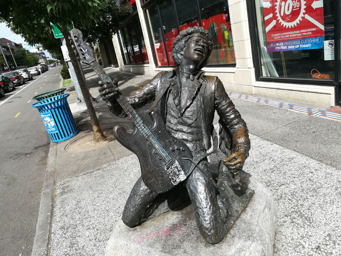A bronze statue of Jimi Hendrix on his knees, playing the guitar