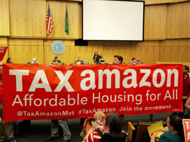 "Seattle residents stand in a government building with a sign declaring, ""tax Amazon, affordable housing for all"""