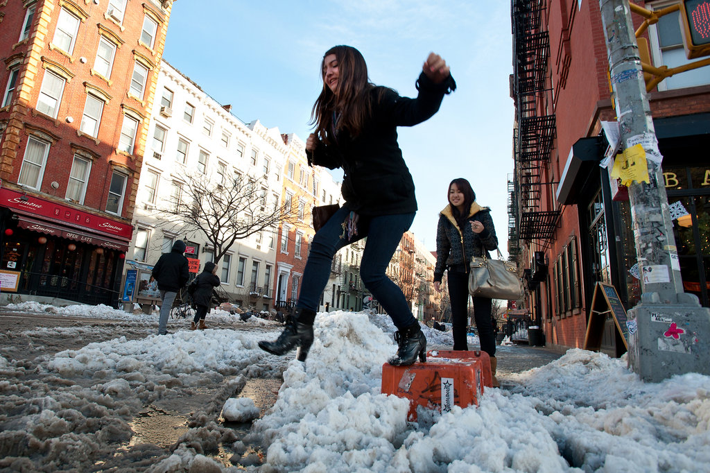Woman stepping over snow on the NYC sidewalk