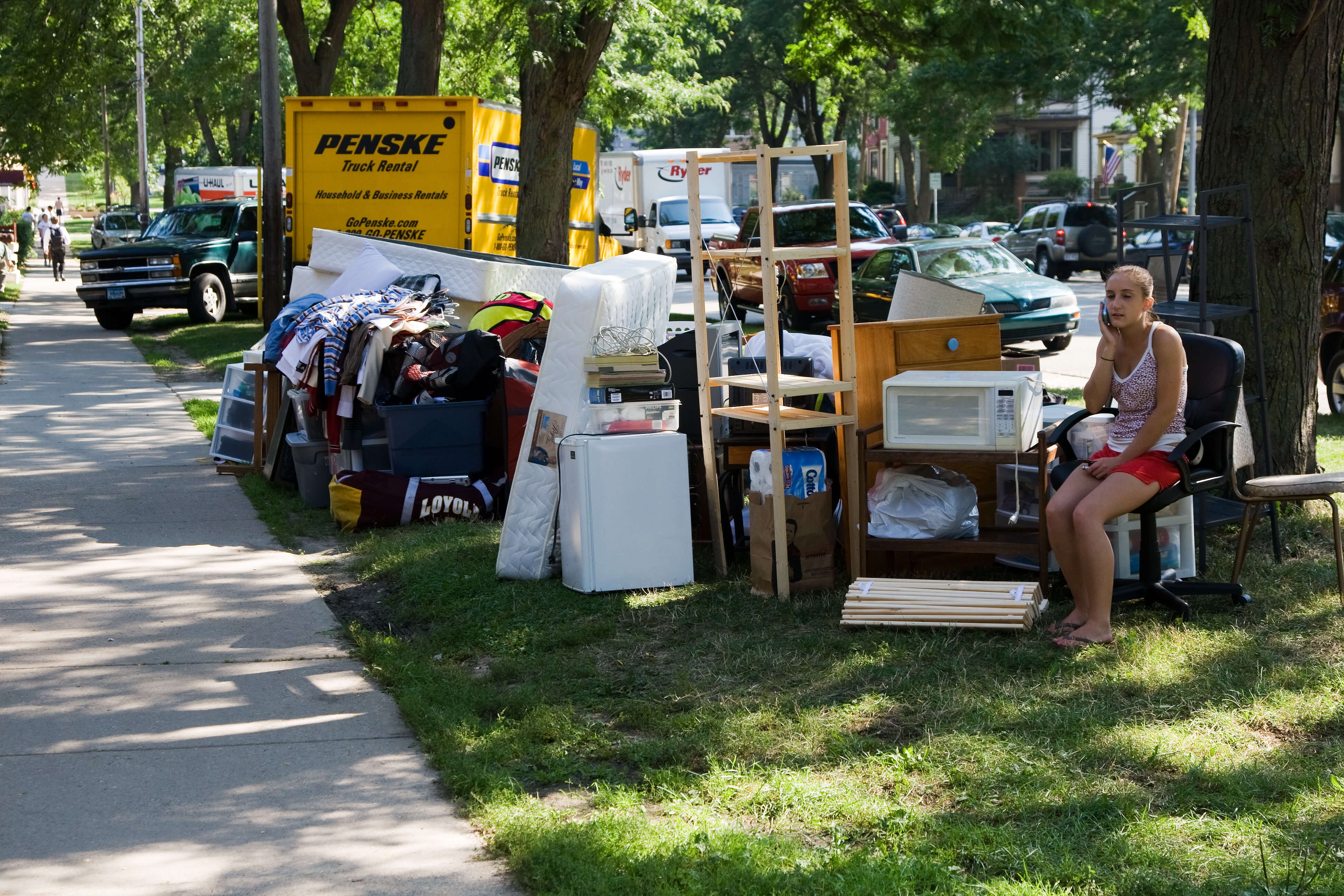 Girl waiting to move in with piles of belongings along the sidewalk