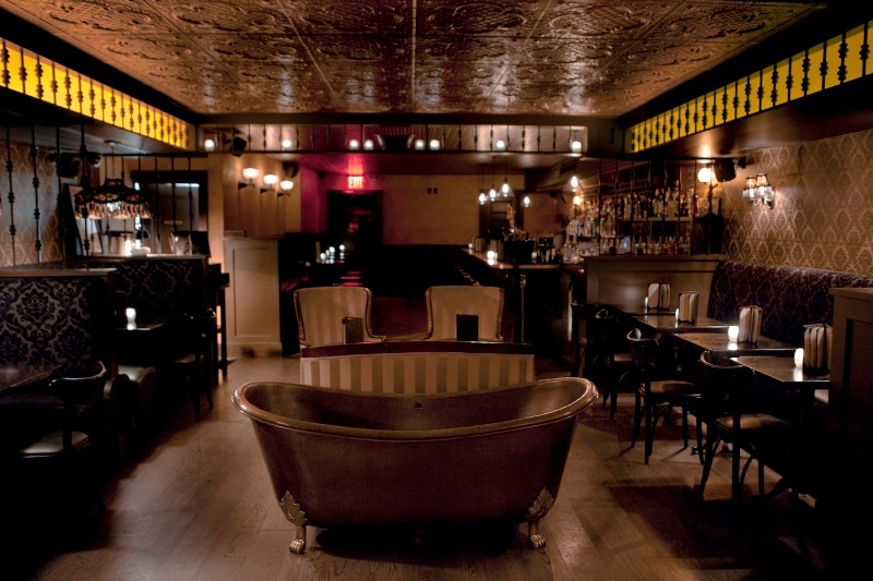 A dark room with decorative tiles on the ceiling and a claw foot tub in the middle of a bar. Tables and booth line the walls and a fully stocked bar can be seen in the back.