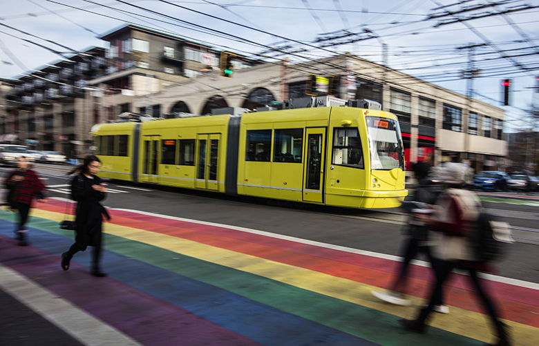 Blurred pedestrians cross a rainbow painted crosswalk as a lightrail car passes through an intersection.