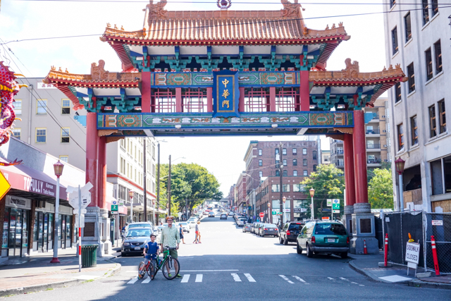 A brightly colored, traditionally asian entryway adorns the entrance to Chinatown as a man and young boy pose in the foreground