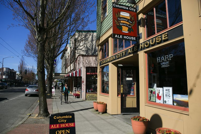 A street level view of Columbia City Ale House against a clear sky and behind a tree lined sidewalk