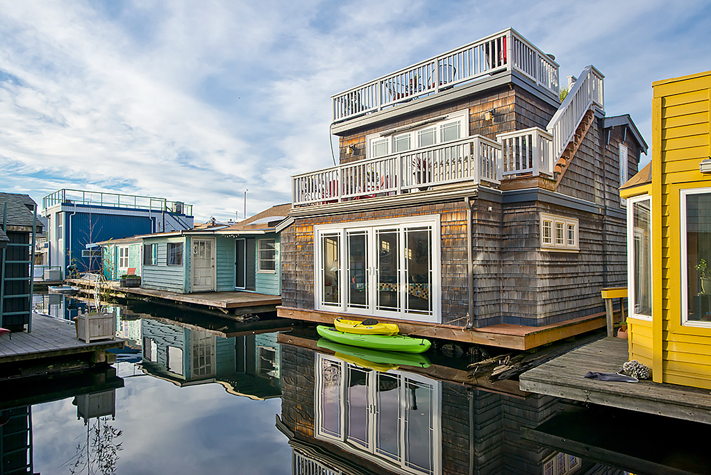 Brightly colored houseboats can be seen lined up long a waterway