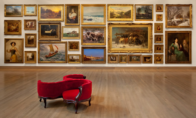 A red velvet couch stands alone on a high varnished hardwood floor surrounded by pieces of classic art in ornate gold frames