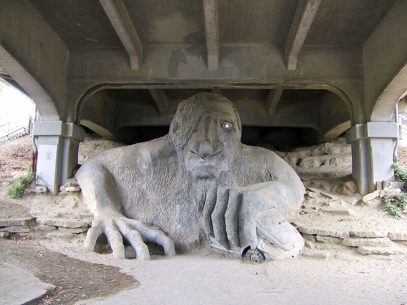 A large concrete troll sculpture appears to crawl from beneath a bridge while crushing a VW Bug