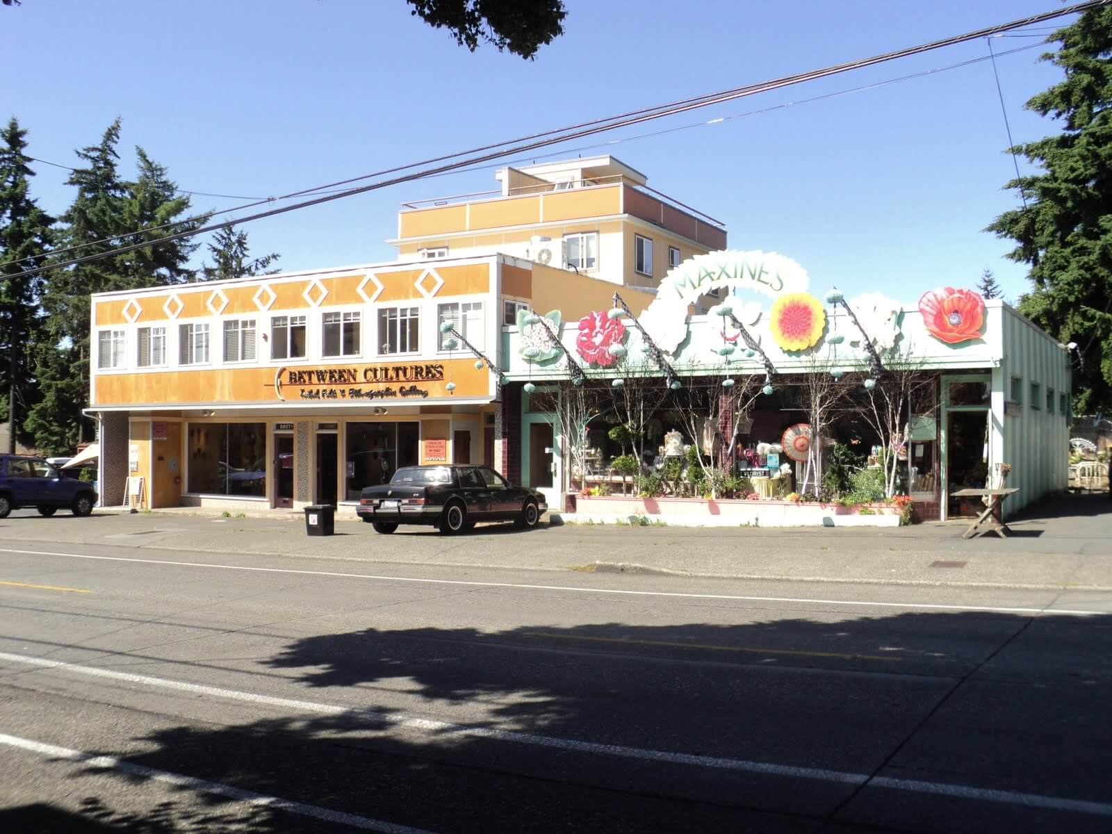 "A large building painted yellow with decorative diamonds sits next to a brightly colored floral shop with the name ""Maxines"""