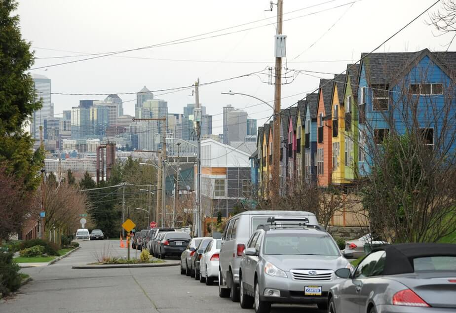 Brightly painted condominiums line a street with limited parking and in the background, a skyline of downtown Seattle can be seen