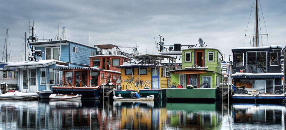 Colorful houseboats lined up in a row in a body of water on a grey overcast day