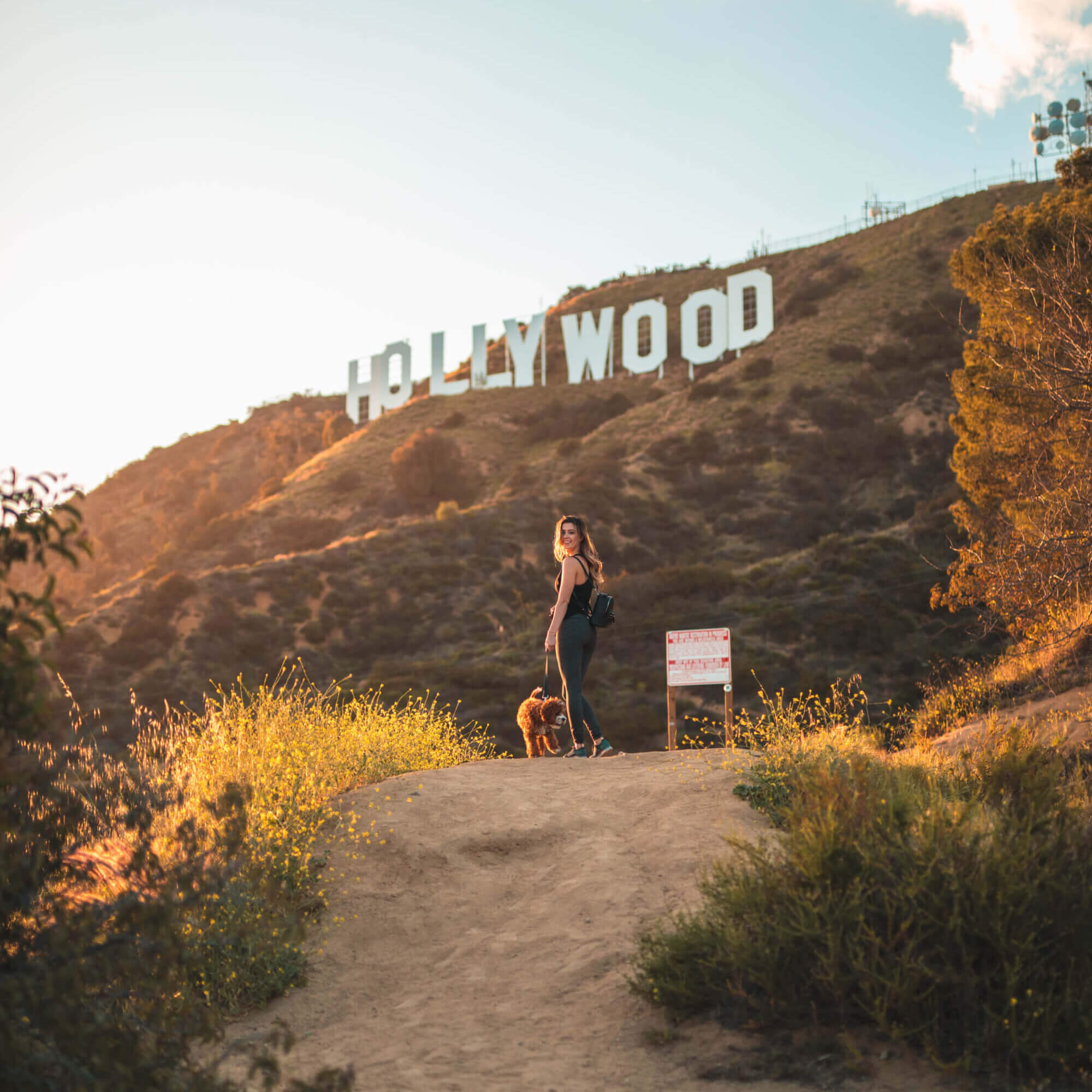 Girl hiking with dog to Hollywood Sign in Los Angeles