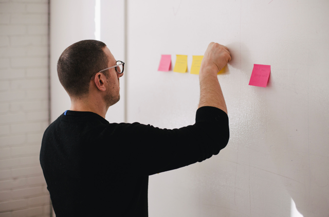 man adding sticky notes to wall