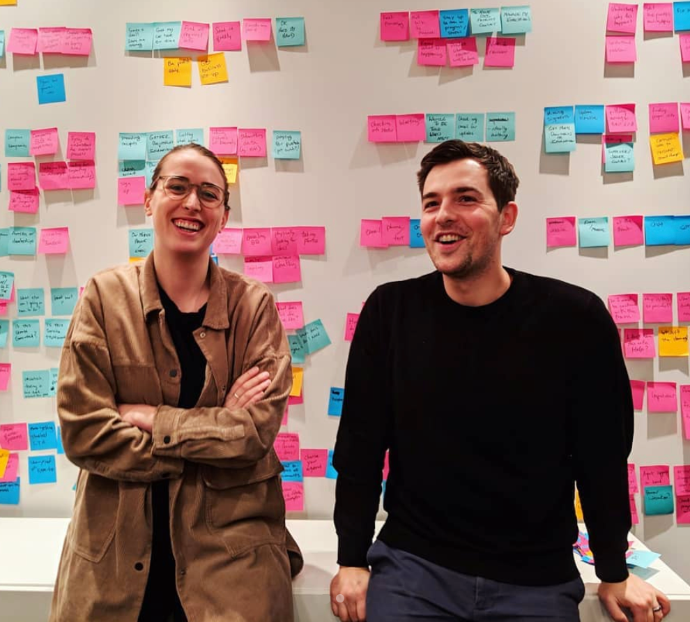 happy coworkers in front of post-its