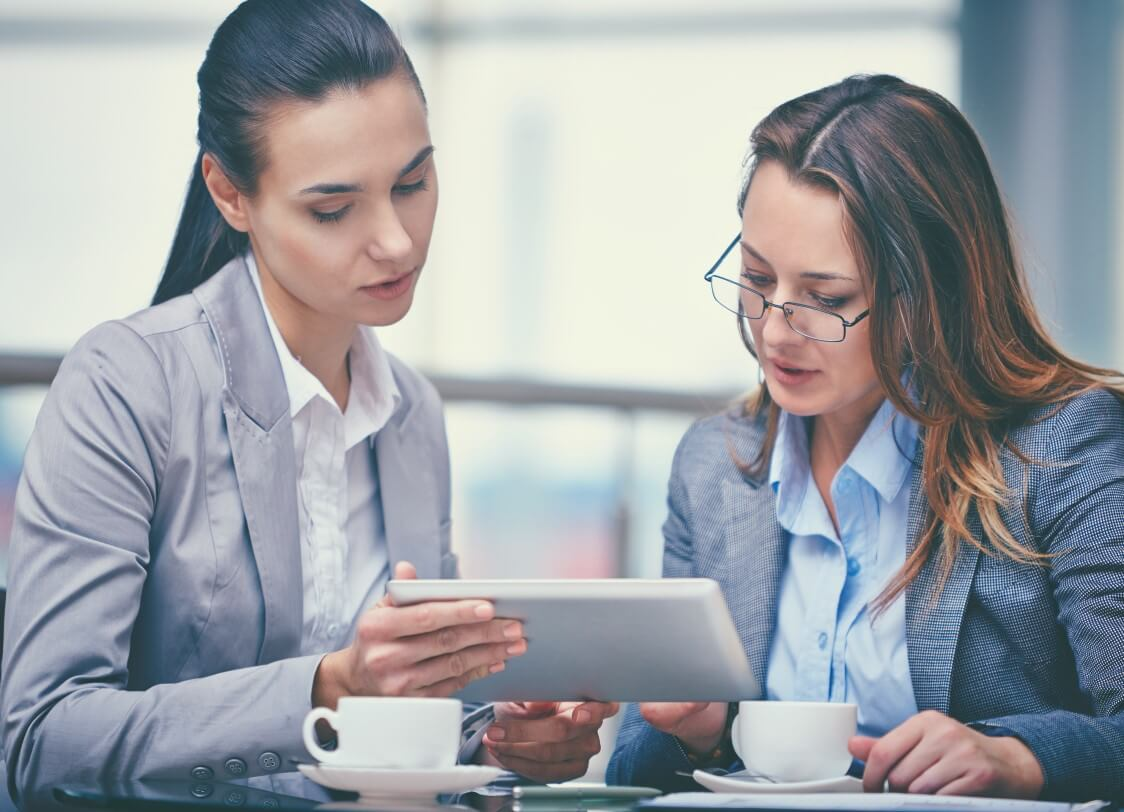 Two women consulting over a tablet