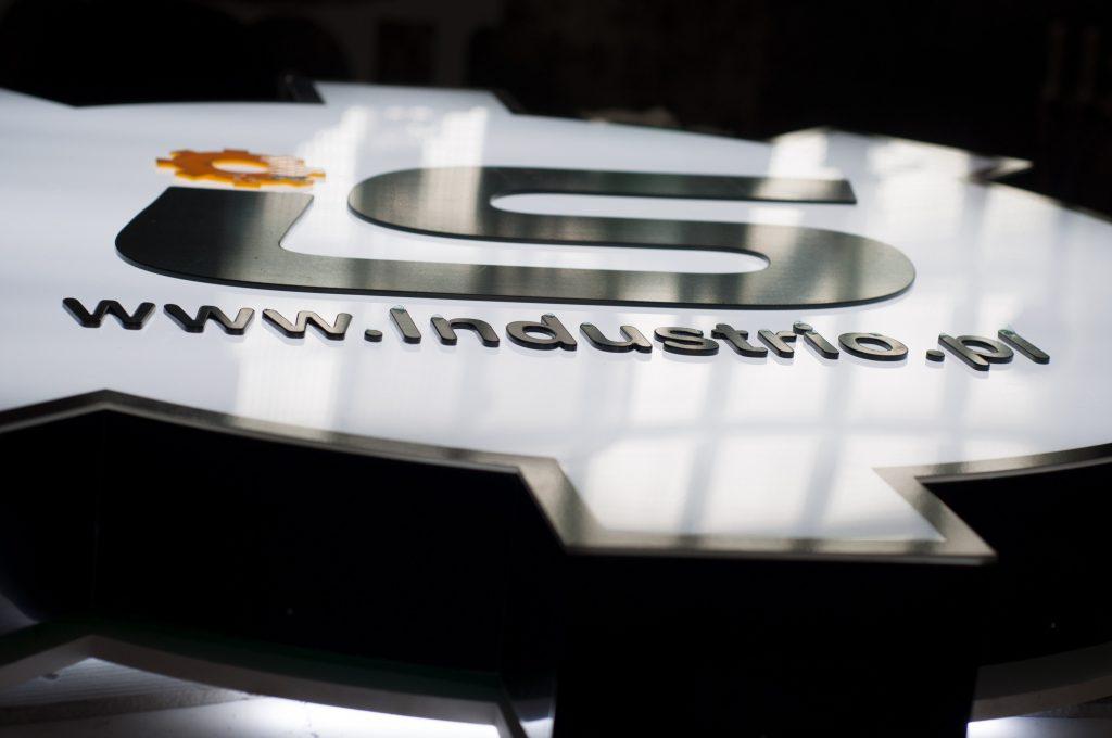 Reklama w kształcie koła zębatego z frontem wykończonym frezowanymi literami z pleksi 3 mm.