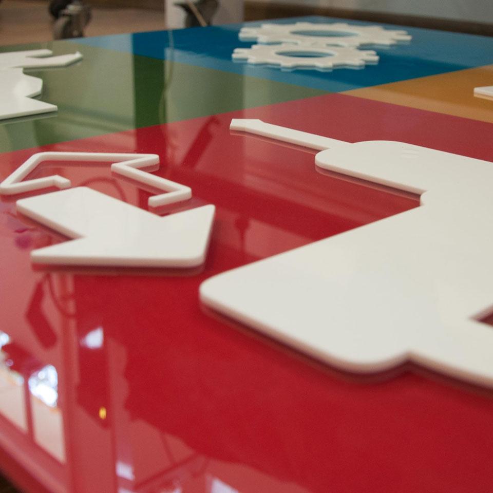 Logotyp z pleksi wycinanany laserowo z elementów z białej pleksi wystające na 10 mm pleksi podklejonej kolorową aplą