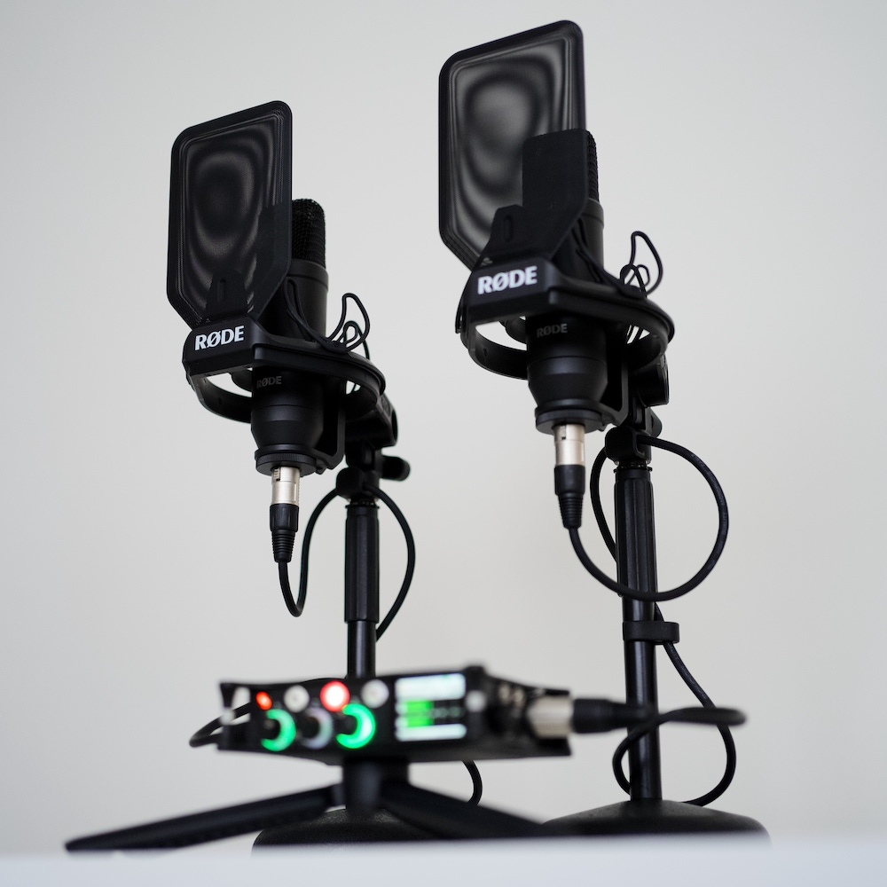 Two podcasting microphones on a white desk with an audio recorder.