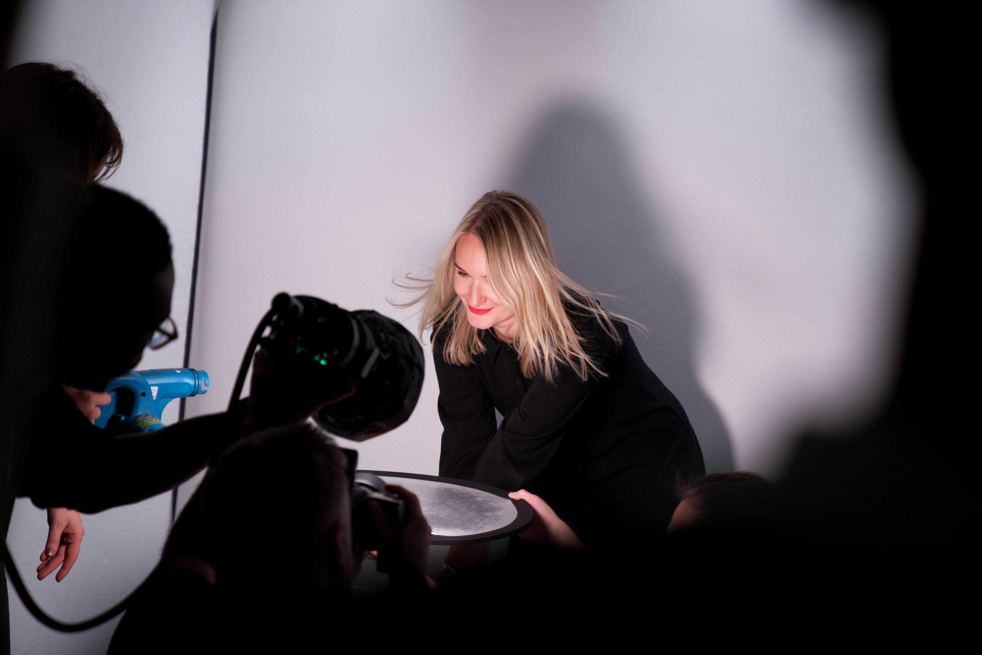 Woman being photographed against a white backdrop