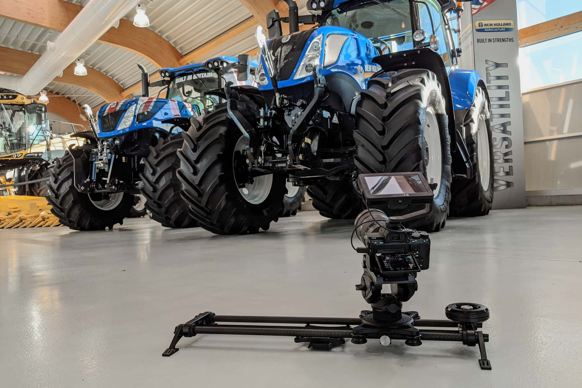Camera filming large tractors in a warehouse