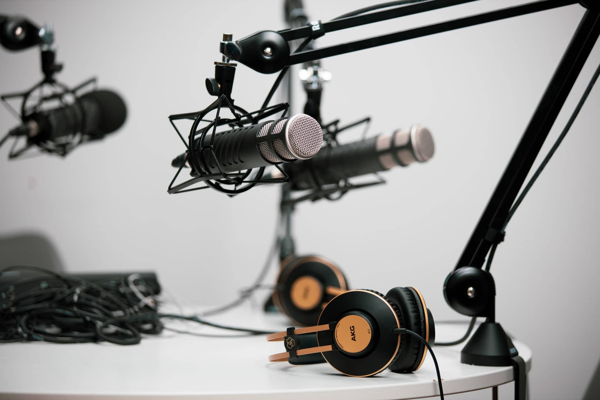 Black Podcast microphone on a scissor arm clamped to a white table