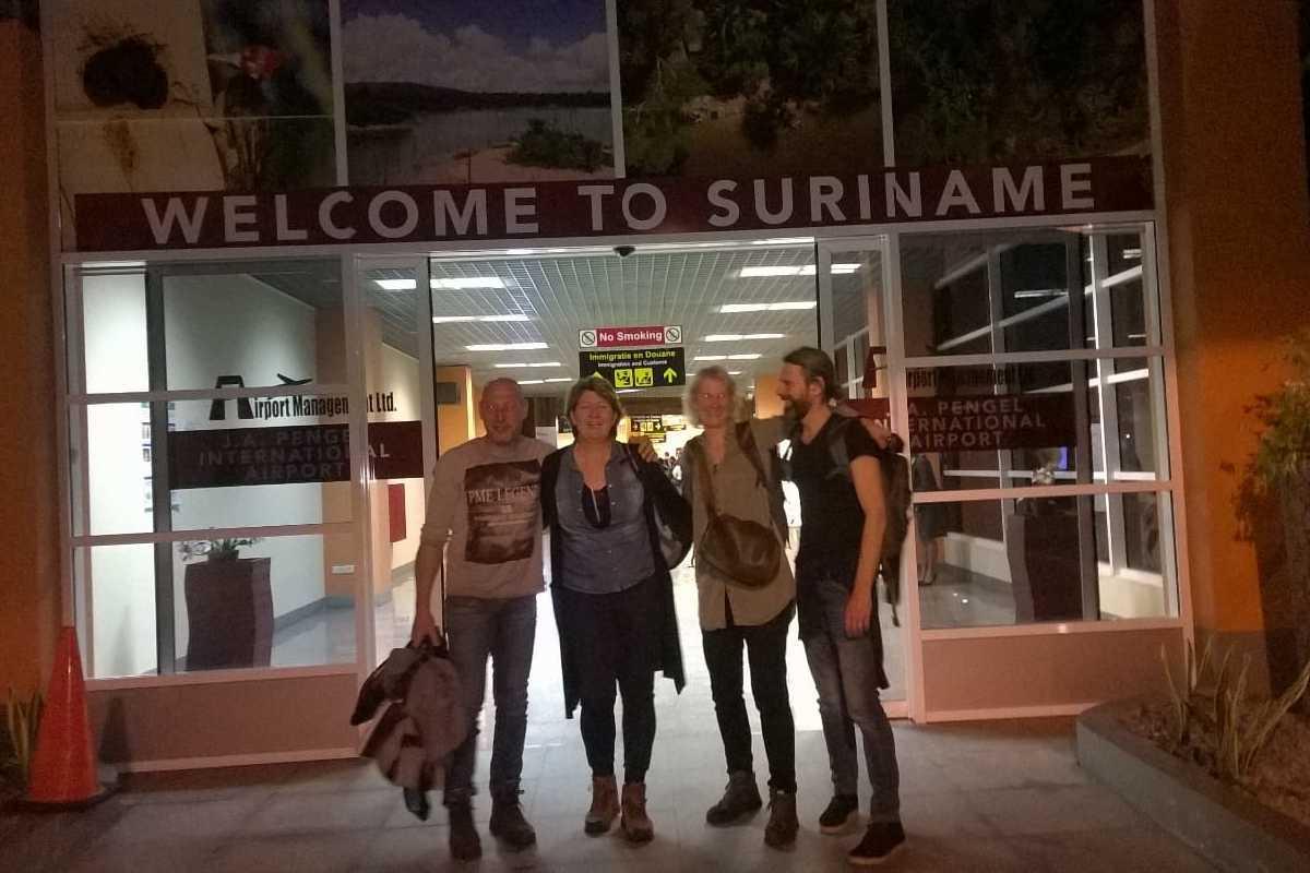 Vrijwilligers poseren voor een foto bij aankomst op de luchthaven van Suriname.