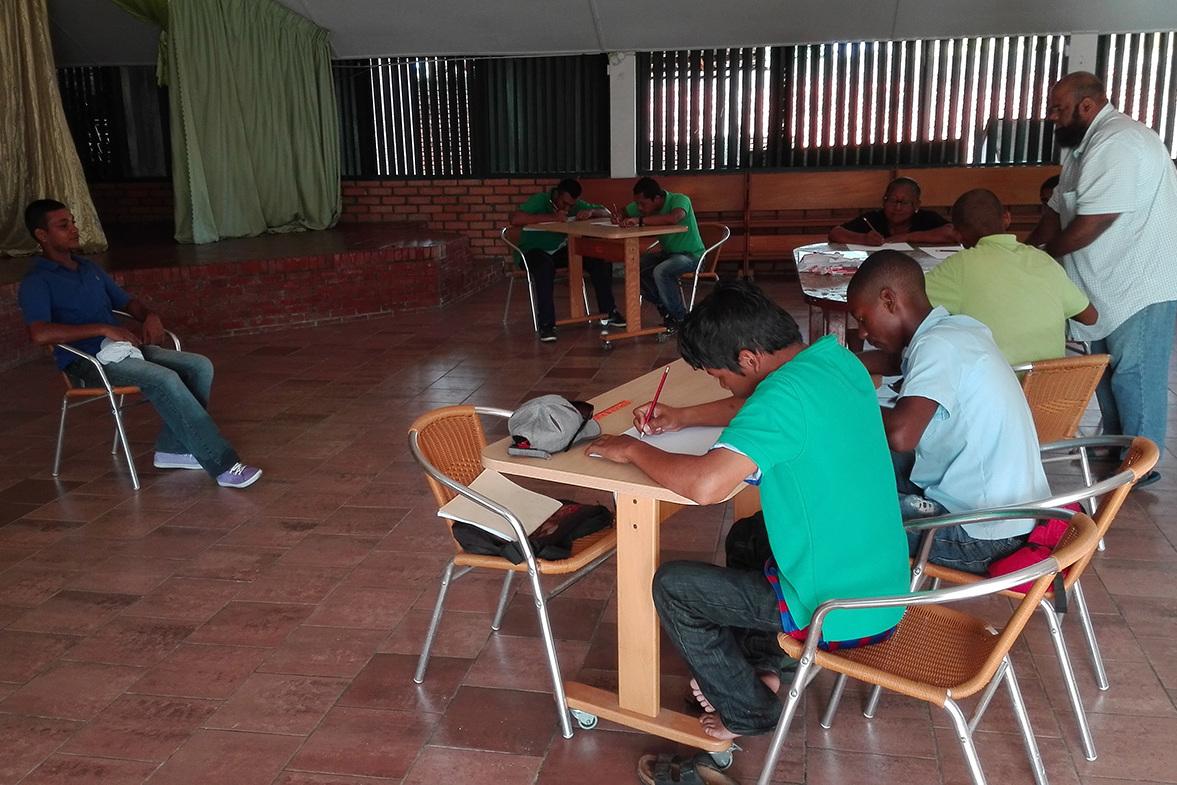 De pupillen zitten in een zaal aan een tafel en concentreren zich op hun tekening.