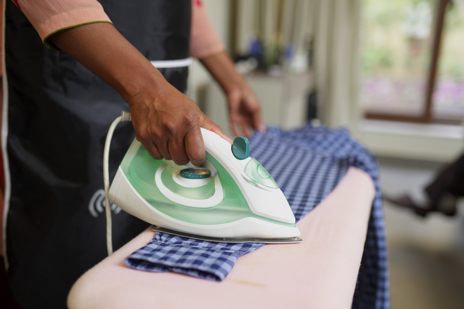 Helper ironing a shirt - available in Islamabad, rawalpindi and lahore through Mauqa Online app