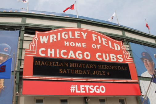 "July 4, 2015 was Military Heroes Day at Wrigley Field, sponsored by Magellan Corporation. The first 10,000 fans received a camouflage Cubs hat courtesy of Magellan. The Military Heroes Day also featured an extended pregame ceremony with an oversized American flag displayed on the field by 100 members of the USO of Illinois, a military ""Take the Field"" experience, decorative bunting in the ballpark and patriotic uniforms for both teams on the field."