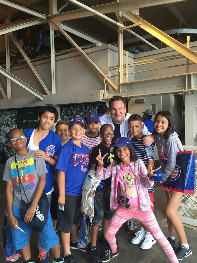 Paying it Forward: Magellan Corporation > Joel Friedman > Northwestern Settlement > Rowe Elementary School. Students with Jeff Garlin at the Chicago Cubs Game