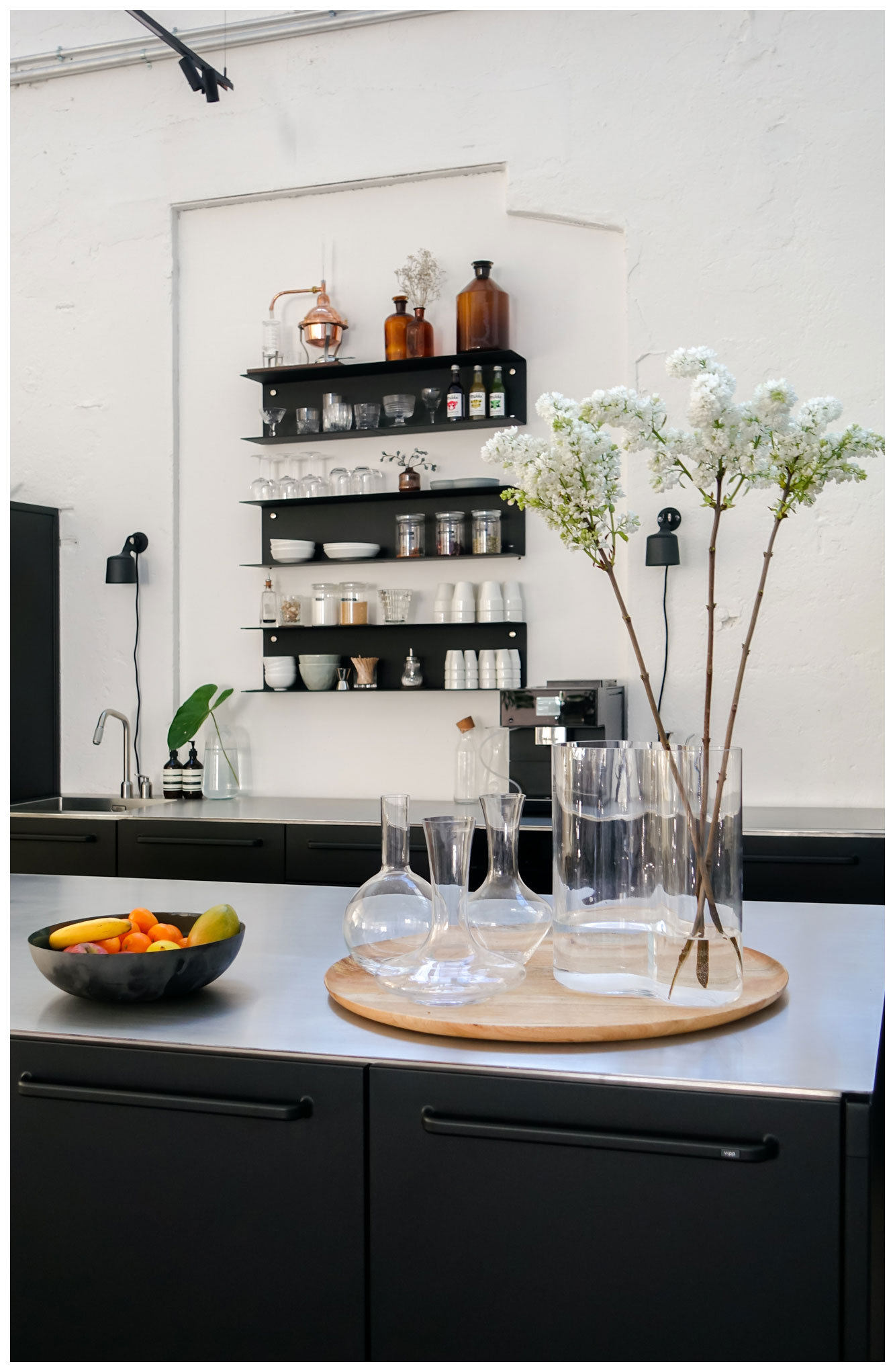 Vipp kitchen in coworking office with flowers on kitchen island