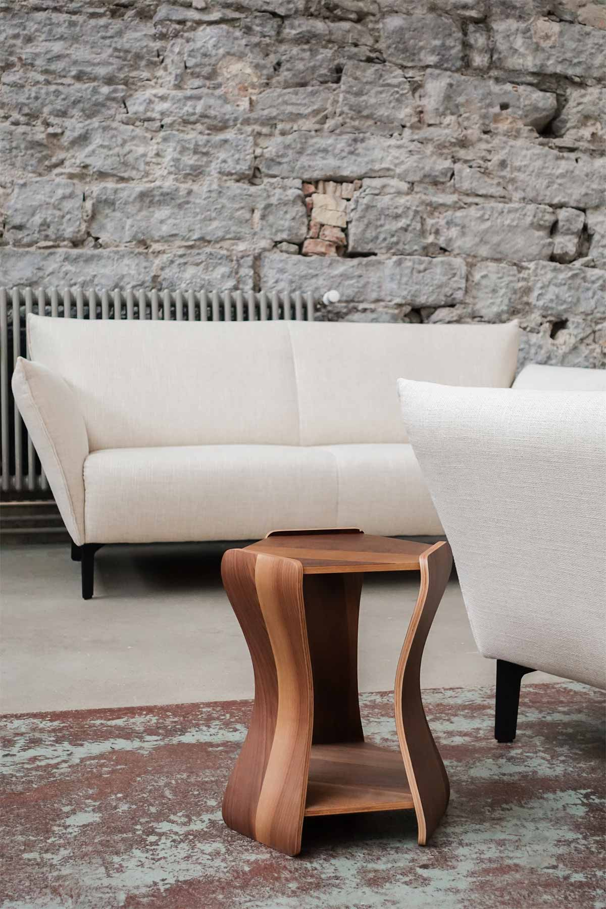 Atelier Pfister wooden stool in front of creme couch and natural stone wall