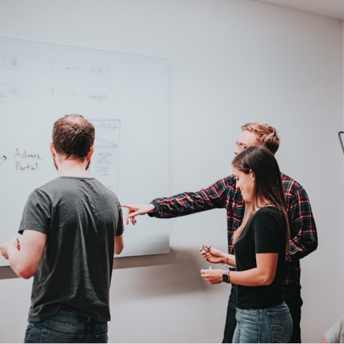 Three people looking at a whiteboard