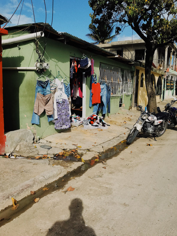 A green house with clothes hanging on its doorframe and windows, parked motorcycles outside and the photographer's shadow in the Dominican Republic