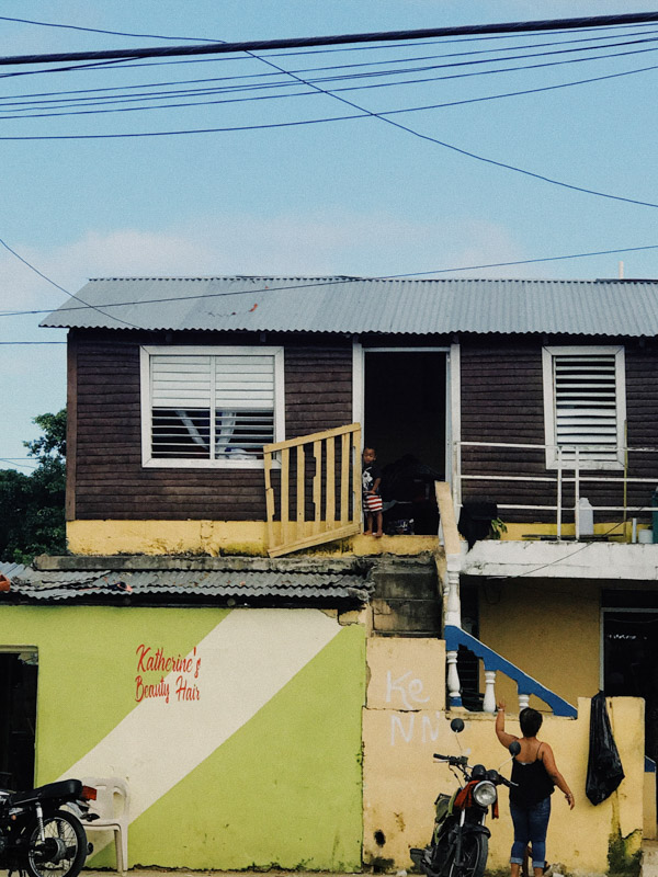 A mother calling her child from outside their home in the Dominican Republic during COVID-19