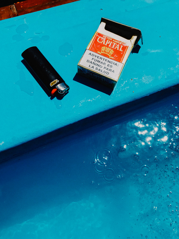 A pack of cigarettes and a lighted by the edge of a pool in the Dominican Republic during COVID-19