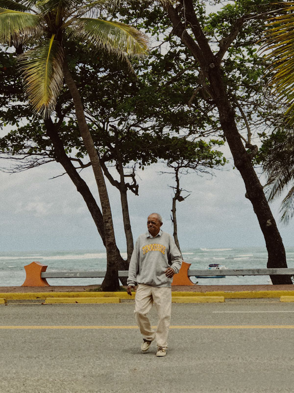 A man crossing a main road overlooking the ocean, lined with tall palm trees in the Dominican Republic during COVID-19