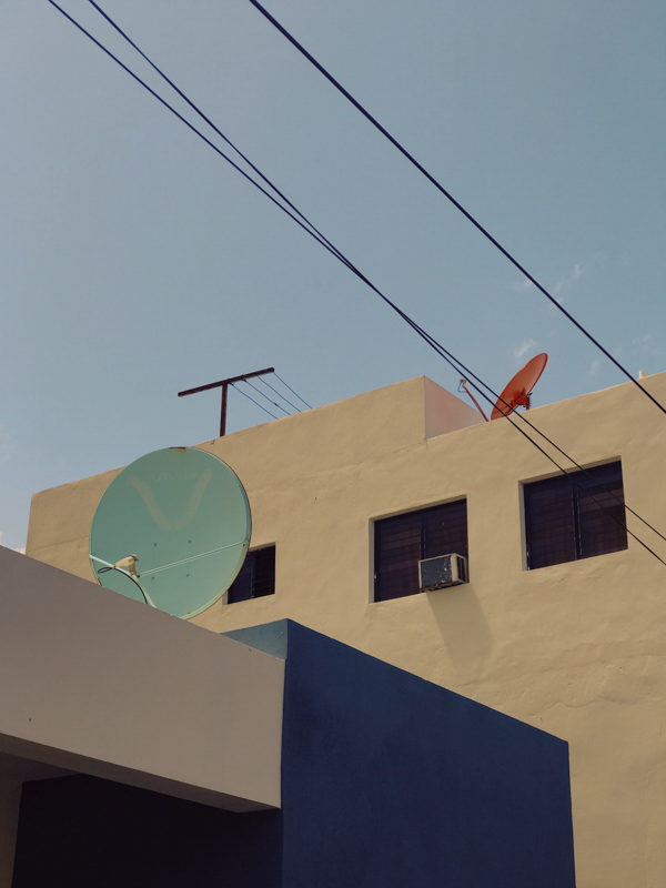 An abstract view of a yellow building and blue satellite dishes in the Dominican Republic during COVID-19