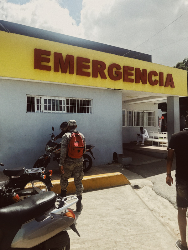 The entrance to an emergency room with two men around motorcycles in front of the building and a man sat on a bench waiting during COVID-19