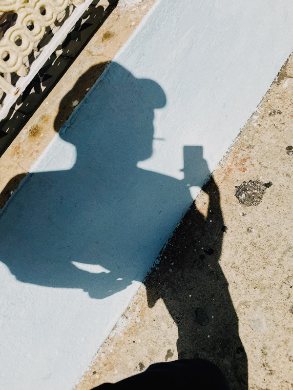 A deformed shadow of a person smoking a cigarette and taking a selfie in the Dominican Republic during COVID-19