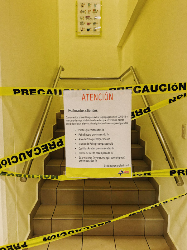 "A yellow corridor with a staircase barred off by emergency tape and a printed sign reading ""Atencion"" about COVID-19 in the Dominican Republic"