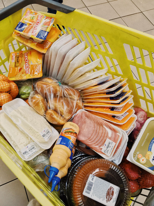 View from above of a yellow shopping basket filled with packaged food in the Dominican Republic during COVID-19