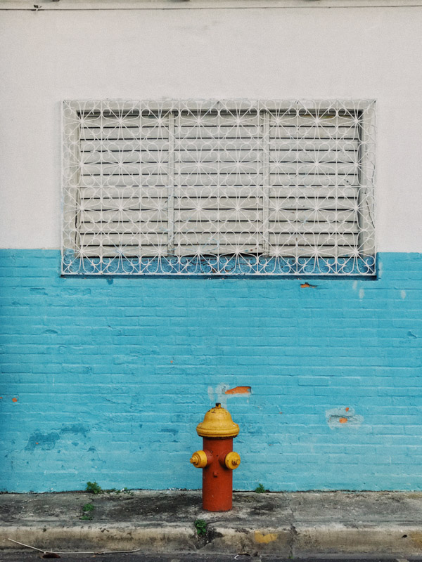 Blue and white wall with window in the middle, and a red and yellow fire hydrant below the window in the Dominican Republic